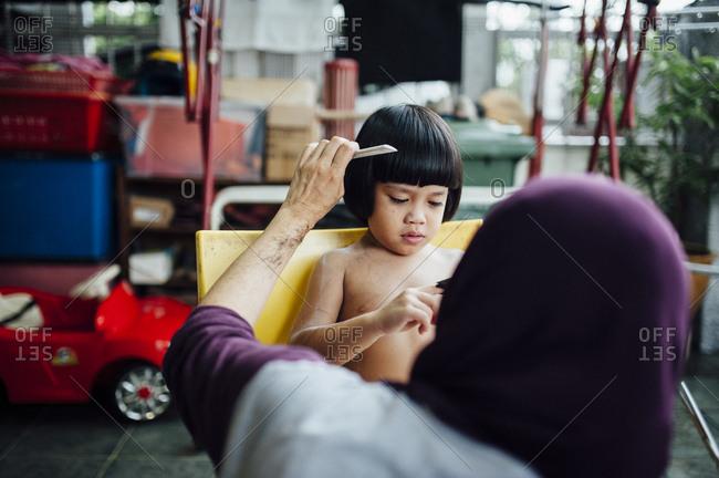 Woman combing Malaysian boy's hair
