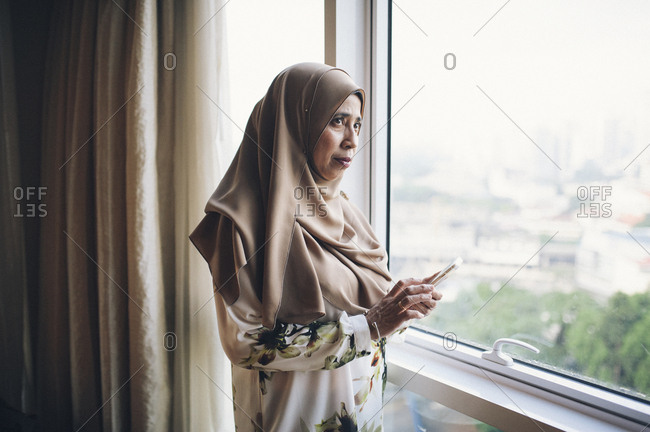 Malaysian woman with phone by window