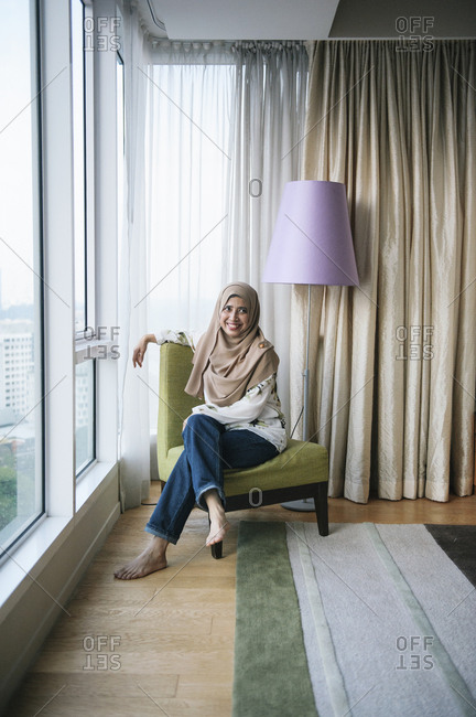 Smiling woman in apartment with view, Malaysia