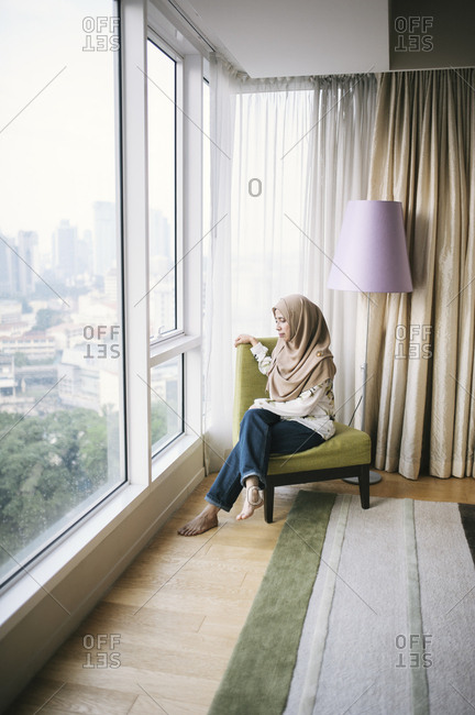 Woman sitting by windows in apartment, Malaysia