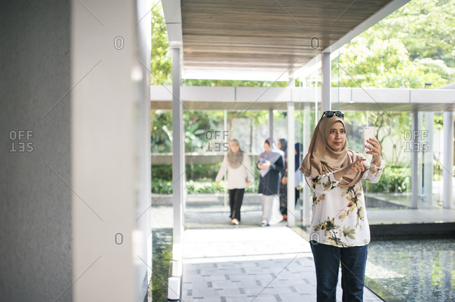 Malaysian woman checking phone outside home