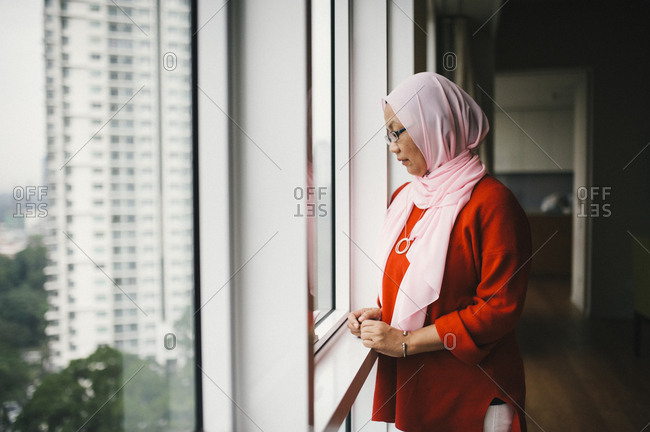Malaysian woman staring out apartment window