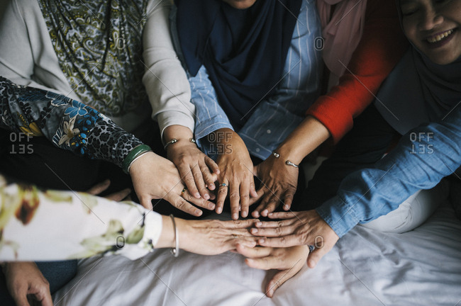 Malaysian female friends with hands together