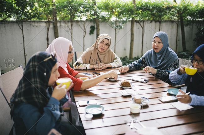 Muslim women eating at outdoor table, Malaysia