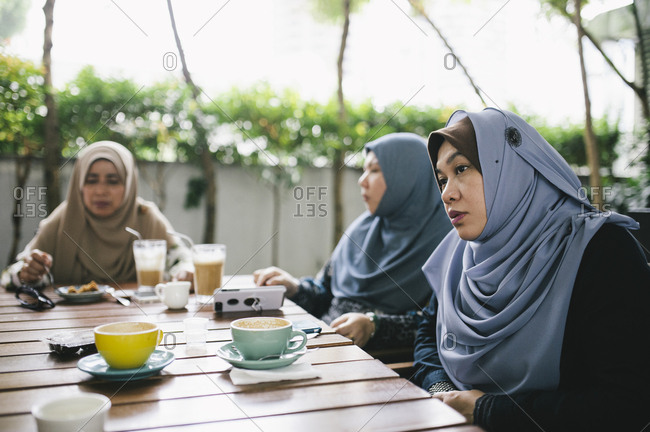 Friends chatting at outdoor table, Malaysia