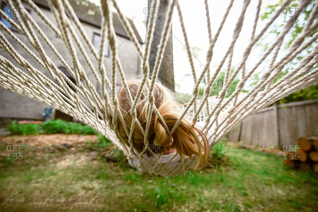 Blond girl lying in hammock