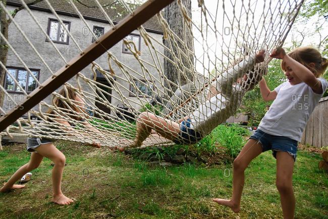 Two girls swinging their friend in hammock