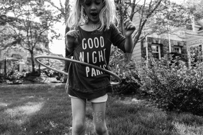 Girl playing with hula hoop in yard