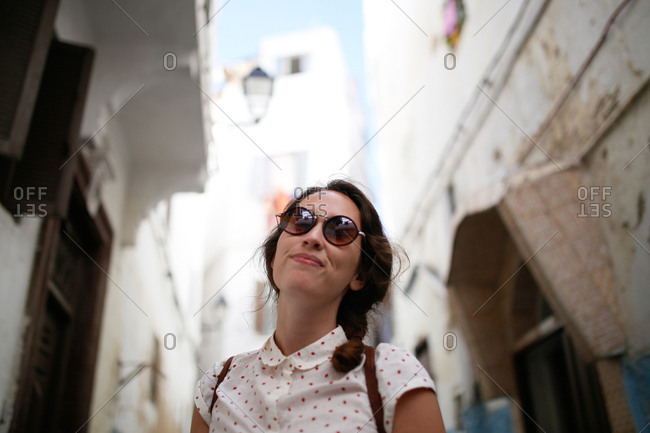 Low angle view of woman in round sunglasses