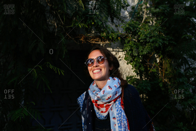 Smiling woman in round sunglasses and scarf