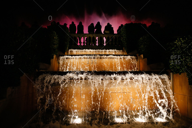 People in silhouette at fountain at night in Spain