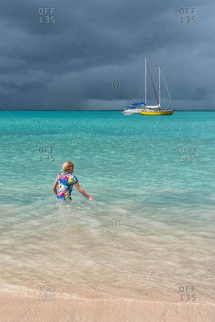 Little girl in the sea near sailboats near Saint Martin Island