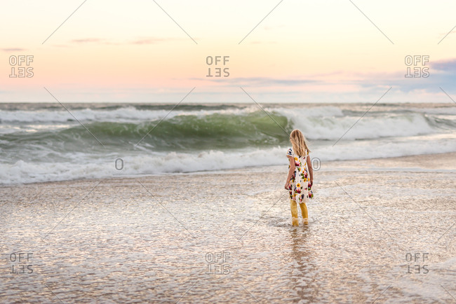 Little girl standing in ocean waves, Outer Banks, North Carolina