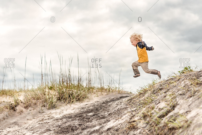 Boy jumping from a hill on Outer Banks, North Carolina