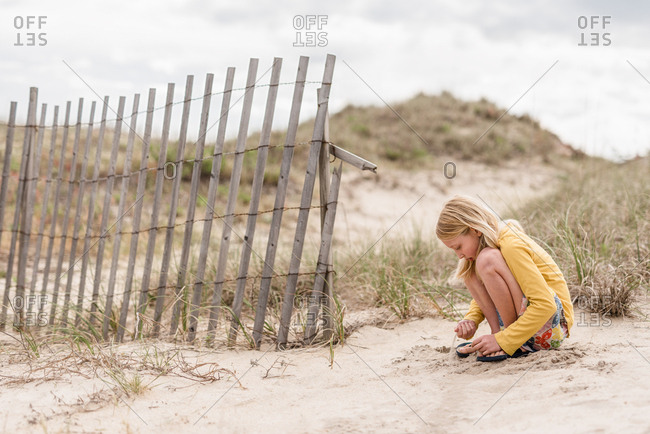 Young girl playing on beach in the sand on Outer Banks, North Carolina