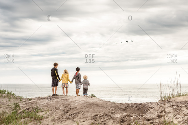 Kids standing on a hill holding hands on Outer Banks, North Carolina