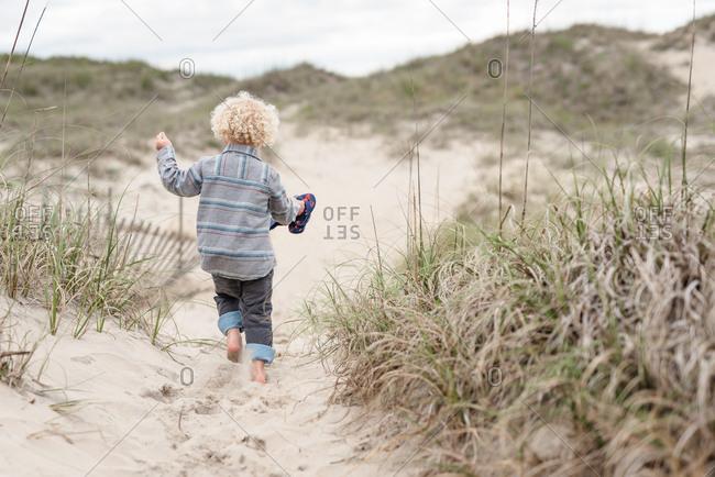 Boy walking on a sandy path on Outer Banks, North Carolina