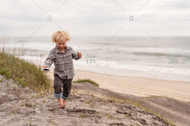 Boy walking on a sandy beach on Outer Banks, North Carolina