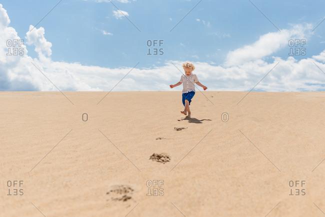 Little boy running down a sandy hill in Jockey's Ridge State Park in North Carolina