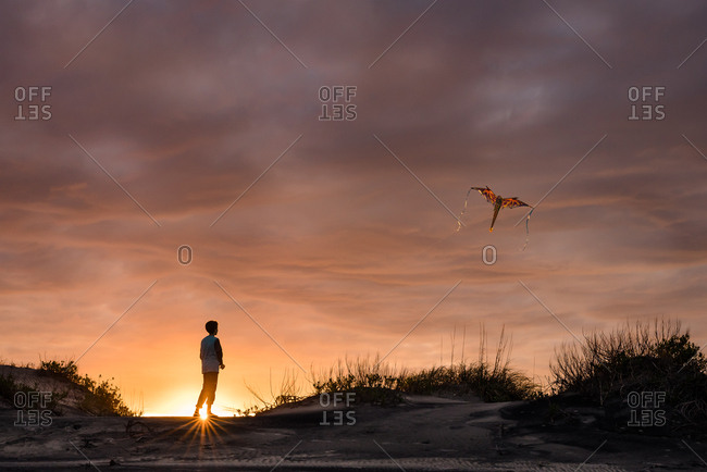 Boy flying a kite at sunset on the Outer Banks, North Carolina