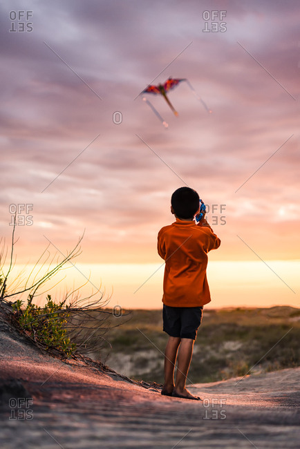 Little boy flying a kite at sunset on the Outer Banks, North Carolina