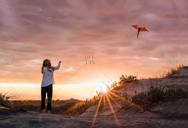 Girl flying a kite at sunset on the Outer Banks, North Carolina