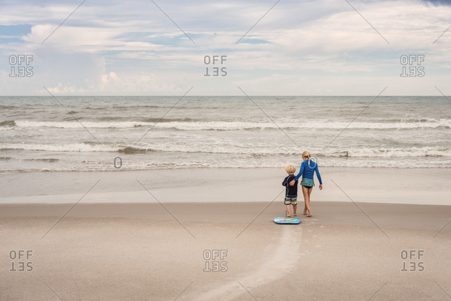 Siblings on a beach with boogie board