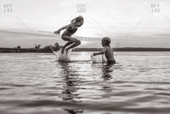 Two children swimming in a lake in black and white
