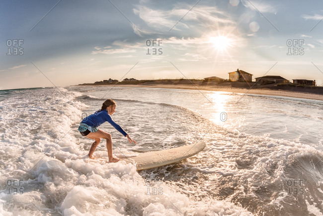 Young girl surfing on a sunny day