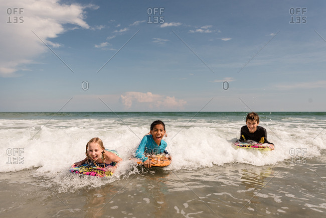 Three kids with boogie boards in the ocean