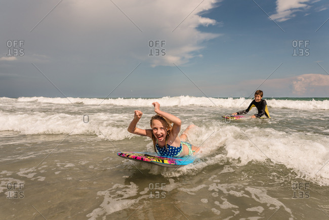 Two kids with boogie boards in the ocean