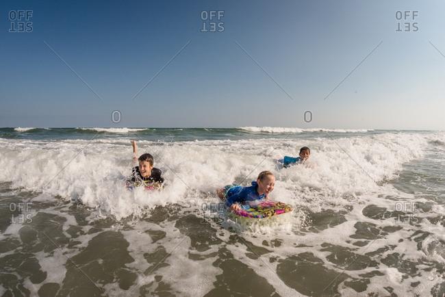 Three kids boogie boarding in the ocean