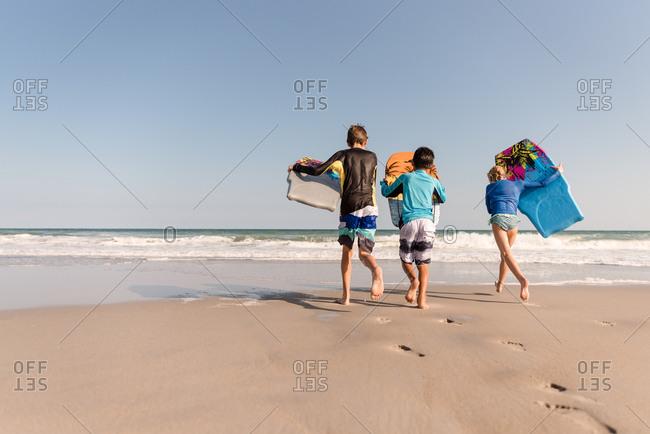Three siblings running with boogie boards toward the ocean