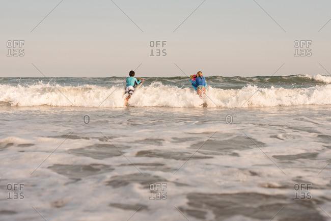 Two kids boogie boarding in the ocean