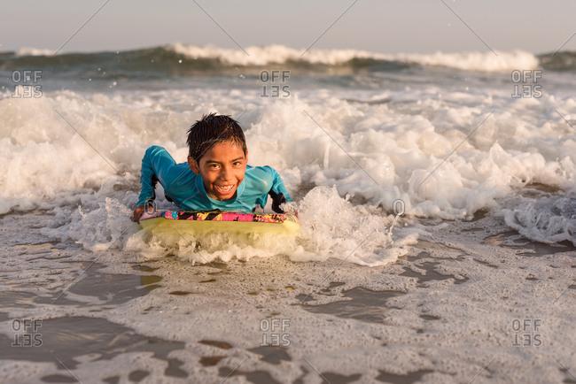 Boy on a boogie board in the ocean under