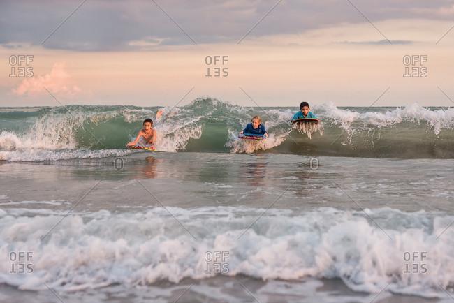 Three kids boogie boarding on ocean waves
