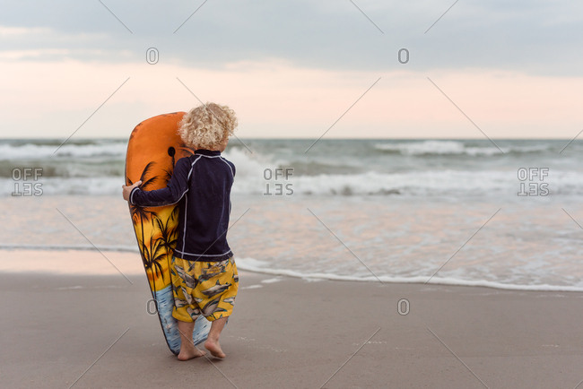 Toddler boy walking with a boogie board on a beach