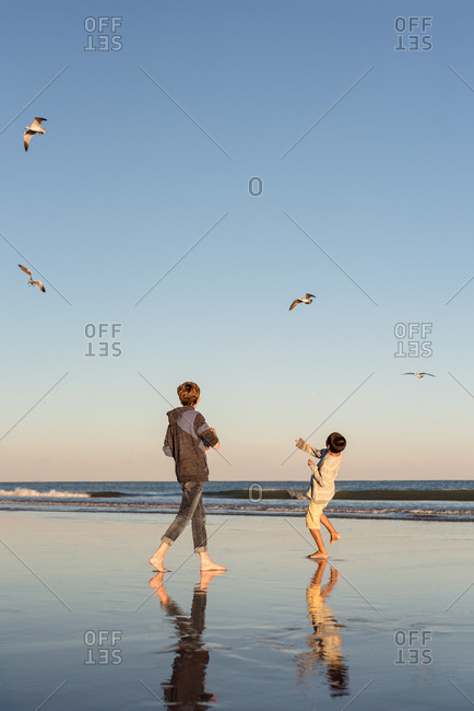 Two boys throwing food up to seagulls on a beach
