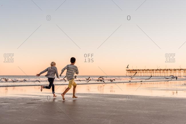 Kids running on beach on Topsail Island, North Topsail Beach, North Carolina