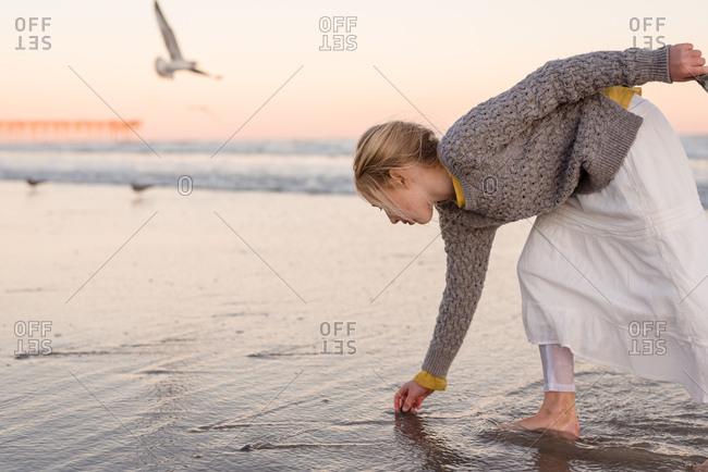 Girl looking for rocks on a beach, Topsail Island, North Topsail Beach, North Carolina