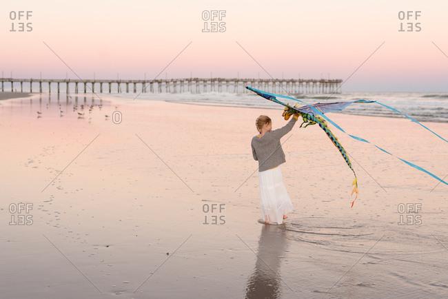 Girl flying kite at sunset on a beach, Topsail Island, North Topsail Beach, North Carolina