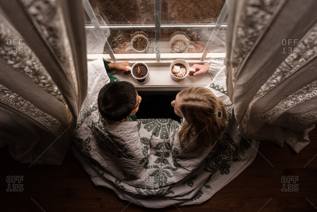 Kids drinking hot chocolate and looking out window