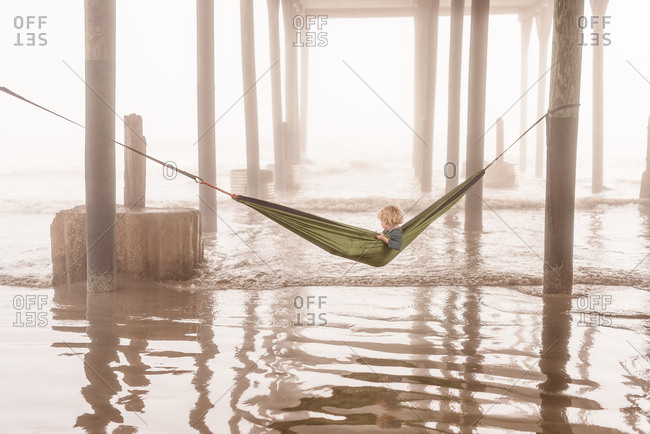 Boy under pier in green hammock in Galveston, Texas
