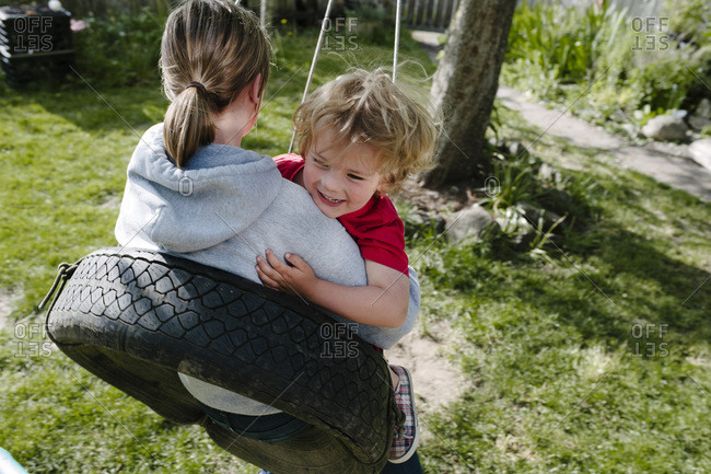 Girl with younger brother on tire swing