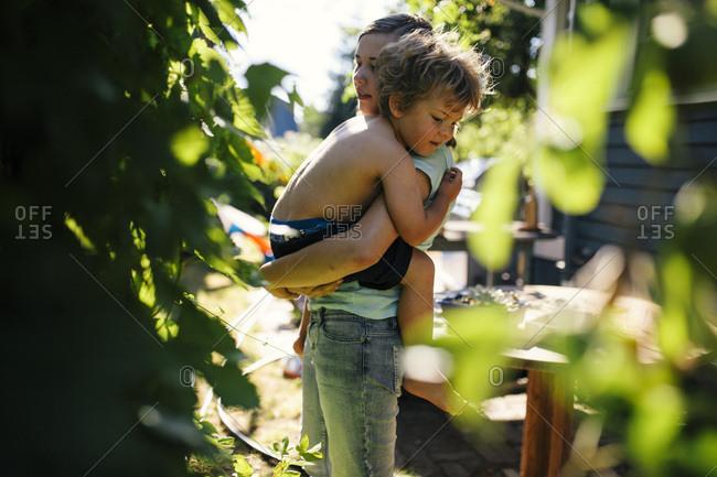 Adolescent girl holding her preschool aged brother in garden