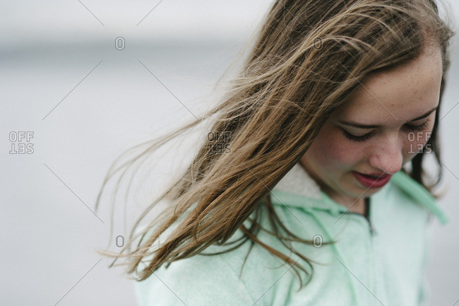 Adolescent girl in with hair blowing in breeze