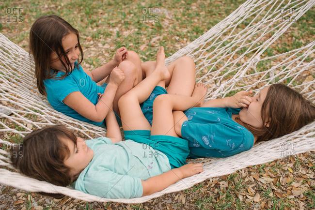Three children lying in a hammock together
