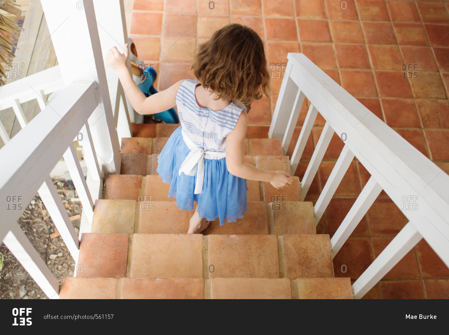 Little Girl Walking Down The Stairs Stock Photo - Download