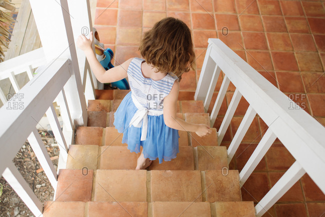 Little girl walking down stairs leading to patio
