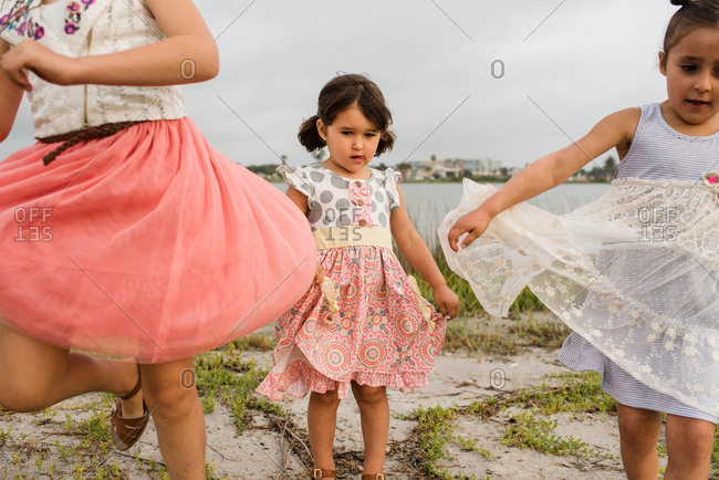 Little girl holding the edge of her skirt while watching her older sisters skip and twirl